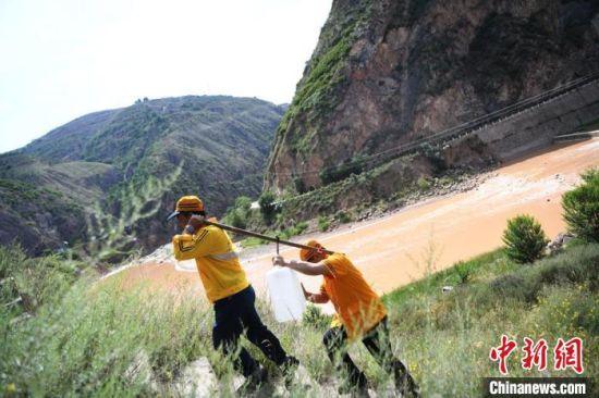 防洪点因为车辆到达不了,值守职工需要肩扛值班期间用的水爬3公里山路到达值守点。 杨艳敏 摄