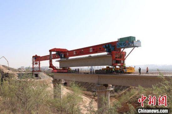 14日10时,中兰铁路宗家梁大桥最后一孔箱梁平稳落到垫梁石上并完成支座灌浆工作。 王子良 摄