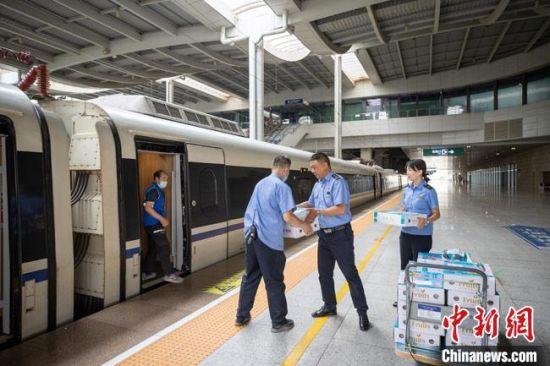 """兰州白凤桃在铁路部门的帮助下运送至高铁站""""乘坐""""动车组列车发往各地。 宋佳龙 摄"""