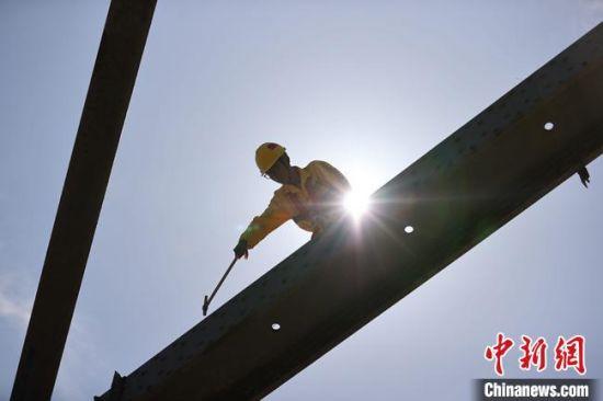 """铁路职工攀爬在黄河大桥上为铁路""""听诊把脉""""。  宋佳龙 摄"""