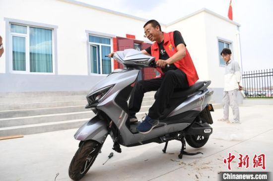 图为舟曲县搬迁移民刘石海在新家展示自己新买的电动车。 杨艳敏 摄