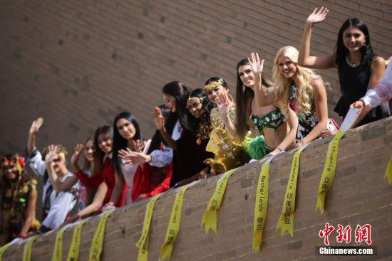6月20日,首届丝路天使总决赛在甘肃嘉峪关举行。各国佳丽通过民族服饰秀、晚礼服秀、泳装秀以及才艺比拼四个环节进行冠亚季军的角逐。图为佳丽们登上嘉峪关城墙拍照合影。中新社记者 熊然 摄