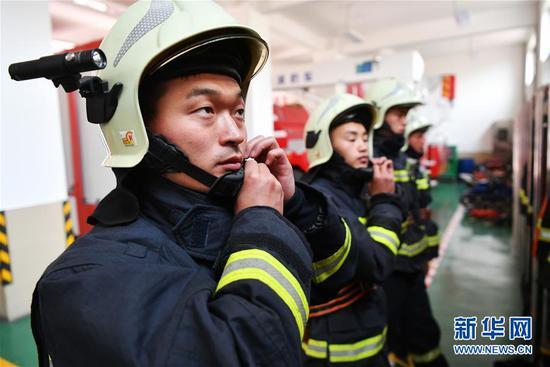 李志亮(左一)和队友穿戴消防救援服,准备执行任务(4月12日摄)。