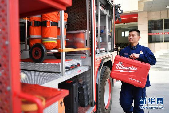 李志亮检查消防车上的消防救援装备(4月11日摄)。 新华社记者 陈斌 摄