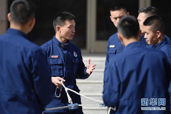 李志亮与队友交流绳索救援经验(4月11日摄)。 新华社记者 陈斌 摄