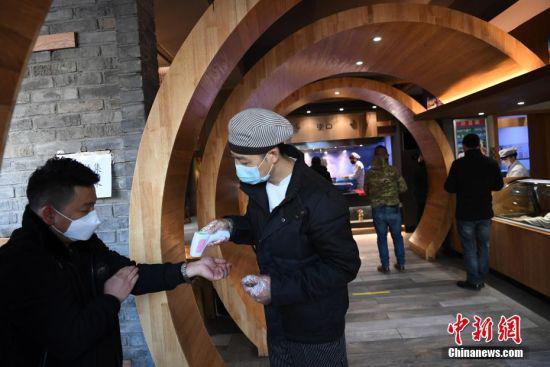2月19日,甘肃省兰州市的一家牛肉面馆由专人为顾客测量体温。