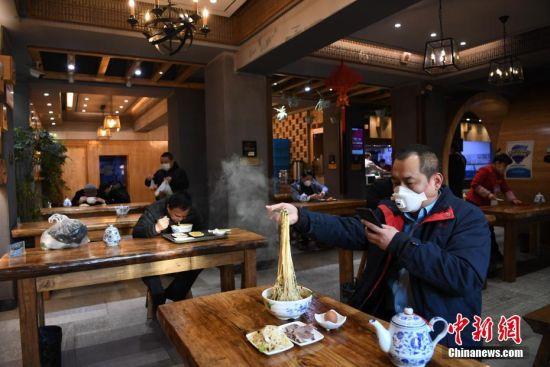 2月19日,甘肃省兰州市的市民在一家牛肉面馆里就餐。