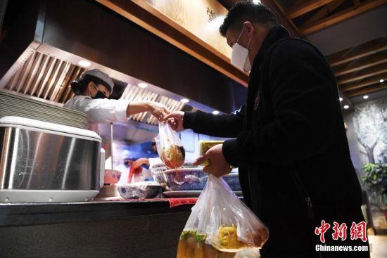 2月19日,甘肃省兰州市的一家牛肉面馆内,一位市民打包取餐。