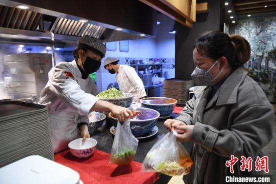 图为日前返回兰州的务工人员,为食客打包牛肉面。 杨艳敏 摄