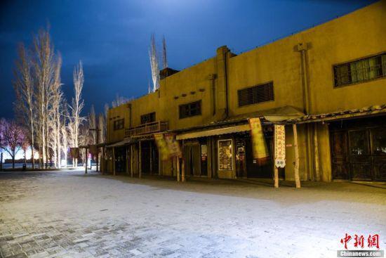 图为3月8日晚,一场春雪降落美丽的敦煌月牙泉小镇。 王斌银 摄