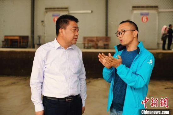 """天祝县委书记李鹏(左)接受自媒体""""码头青年""""主编林飞(右)采访。"""