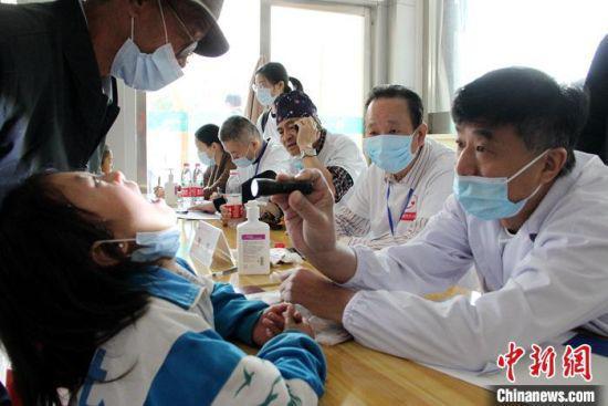 图为医生为患儿进行术前检查。