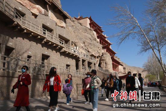 游客在敦煌莫高窟游览,感受敦煌文化魅力。张晓亮 摄
