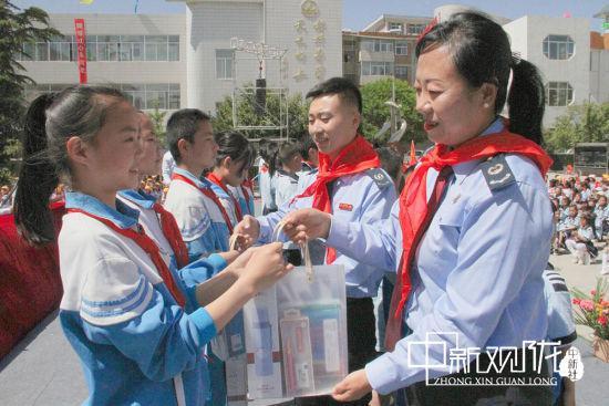 图为庆城县税务局党委委员、副局长司继华为贫困儿童赠送学习用品。