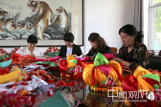 端午节临近,庆阳锦篮文化传播有限公司组织绣娘在生产基地赶制香包 。