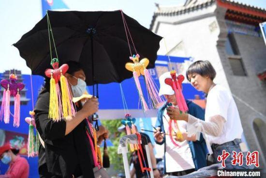 """端午节期间,甘肃""""非遗+民俗""""游受追捧。图为在假日期间举行的非遗节会上,游客挑选手工香包。 杨艳敏 摄"""