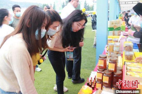 图为消费者查看蜂蜜产品。 陇南市委宣传部供图