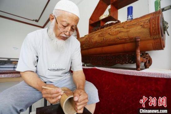 图为吴云生在竹子上手工雕刻,身后是他最得意的一件雕刻作品,箱身雕刻了清明上河图局部。 高展 摄