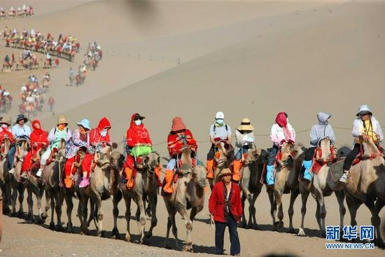 月牙泉边、鸣沙山上骑骆驼的游客。新华社记者 刘诗平 摄