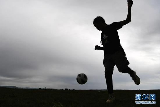 7月14日,河曲马场小学学生丹增喇巴在草原上踢足球。新华社记者 陈斌 摄