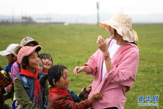 7月14日,河曲马场小学老师余妙妍(右一)在草原上和孩子们做游戏。新华社记者 陈斌 摄