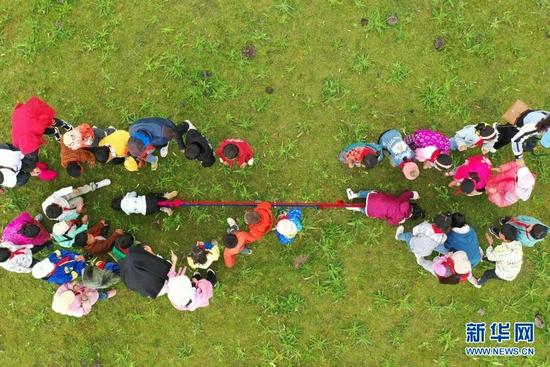 7月14日,河曲马场小学的孩子们在草原上进行拔河比赛(无人机照片)。新华社记者 杜哲宇 摄