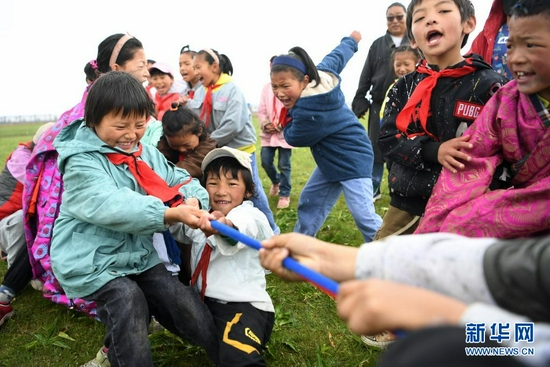 7月14日,河曲马场小学的孩子们在草原上进行拔河比赛。新华社记者 陈斌 摄