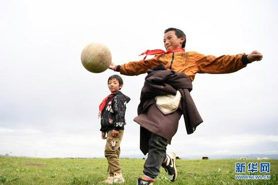 7月14日,河曲马场小学学生参交罗布藏(右)和同伴在草原上踢足球。新华社记者 陈斌 摄