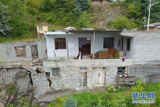 在舟曲县果耶镇虎家梁村,虎吾成在自家院落中向外观望(8月5日摄,无人机照片)。新华社记者 范培珅 摄