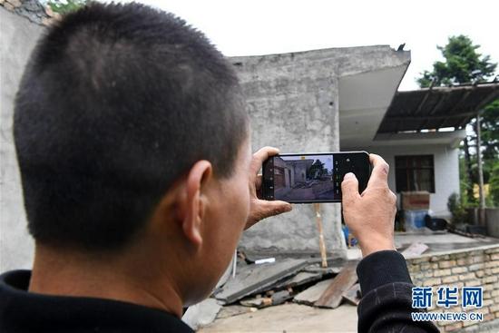 在舟曲县果耶镇虎家梁村,虎吾成用手机拍摄自家老屋(8月5日摄)。新华社记者 范培珅 摄
