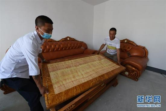 8月7日,在兰州新区的新家,虎吾成(右)在村民帮助下摆放沙发。新华社记者 范培珅 摄