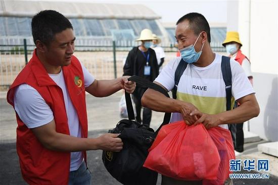 8月7日,在兰州新区,志愿者引导虎吾成(右)前往新家。新华社记者 范培珅 摄