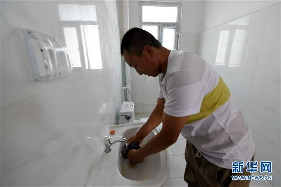 8月7日,虎吾成在兰州新区的新家卫生间洗手(8月7日摄)。新华社记者 范培珅 摄