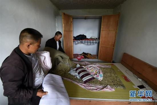 在舟曲县果耶镇虎家梁村,虎吾成(左二)收拾打包被褥(8月5日摄)。新华社记者 范培珅 摄
