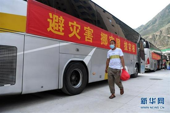 在舟曲县地质灾害避险搬迁首批搬迁群众转运点,虎吾成领取路餐后准备乘车前往兰州新区(8月7日 摄)。新华社记者 范培珅 摄
