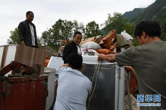 在舟曲县果耶镇虎家梁村,虎吾成(左二)往搬家车辆上搬运物品(8月5日摄)。新华社记者 范培珅 摄
