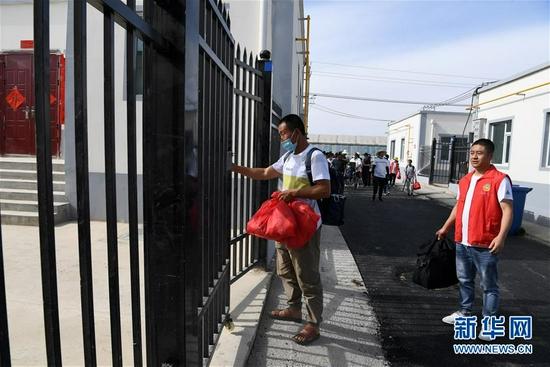 8月7日,在兰州新区,虎吾成(左一)在志愿者的引导下来到新家门口。新华社记者 范培珅 摄