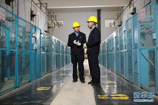 8月17日,石瑾(左)和同事在高压室内巡视。新华社记者 杜哲宇 摄