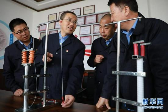 8月17日,石瑾(左二)和同事在模型前对自主研制的设备进行改进探讨。新华社记者 杜哲宇 摄