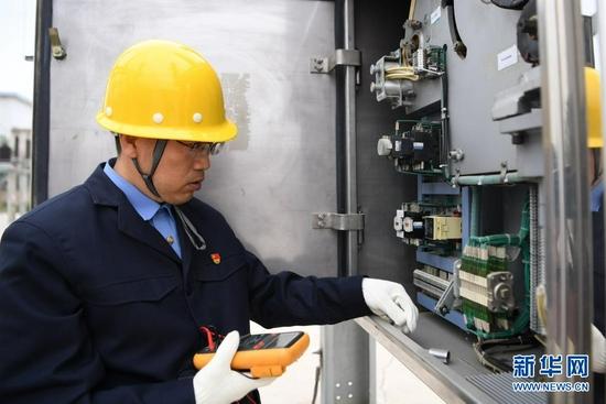 8月17日,石瑾在检查高压断路器机构箱内设备状态。