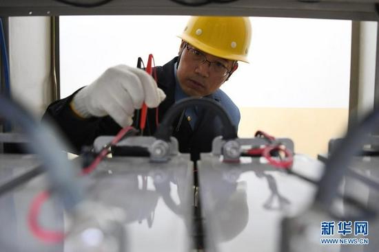 8月17日,石瑾在测量蓄电池参数。新华社记者 杜哲宇 摄