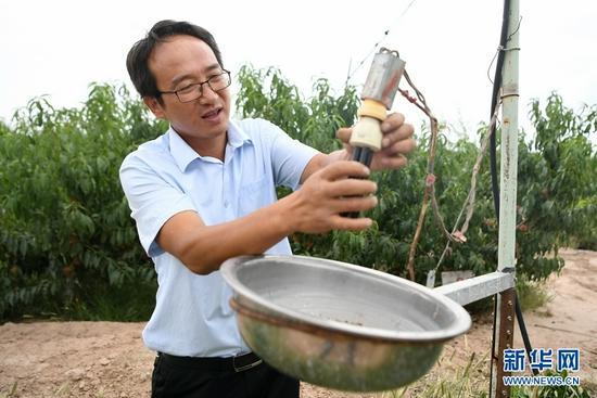 8月18日,方志利在检查除虫设备。新华社记者 陈斌 摄