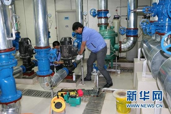 工作人员检修地源热泵(资料照片)。(敦煌研究院供图)