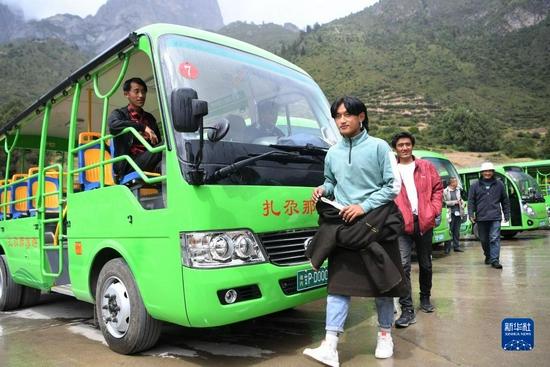 扎尕那村的几位村民从景区观光车停靠点走过(8月28日摄)。新华社记者 陈斌 摄