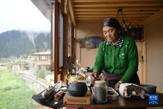 扎尕那村村民云草在自家的民宿里整理茶台(8月28日)。新华社记者 陈斌 摄