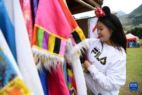 一名游客在扎尕那景区挑选藏族服饰体验民族风情(8月28日摄)。新华社记者 杜哲宇 摄