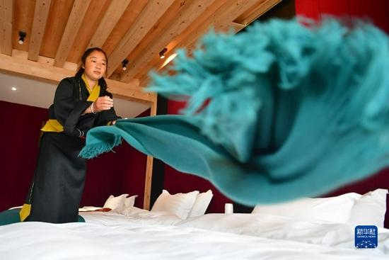 扎尕那村村民仁青卓玛在自家的民宿里整理床铺(8月28日)。新华社记者 陈斌 摄