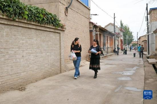 8月31日,陇西县靛坪小学教师杨慧君(右)和陇西特殊教育学校教师郭丽娟在前往小州家的途中。新华社发(王紫轩摄)