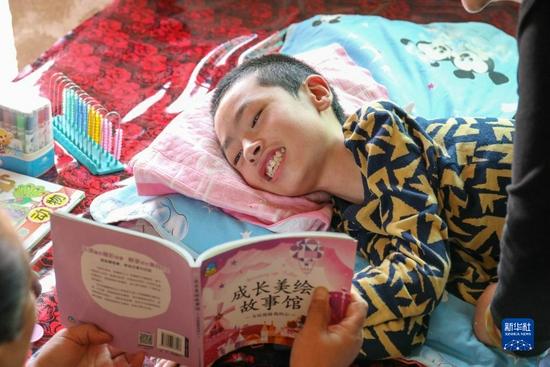 8月31日,侧卧在床的小州在两位送教老师的引导下朗读《珍珠鸡》。新华社发(王紫轩摄)