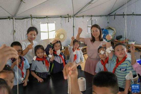 9月2日,胡家大院扎染体验馆的工作人员辅导渭州学校的学生们体验扎染。新华社发(王紫轩 摄)